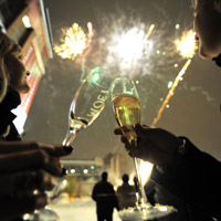 Two women toast as fireworks explode dur